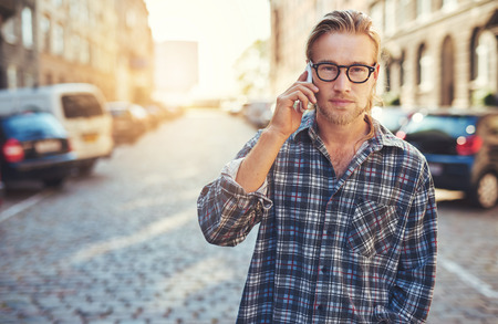 man with glasses: closeup portrait of young man talking on his cellphone in the city