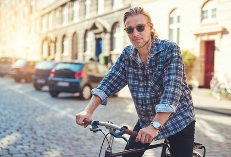 hombre sentado: Hombre joven en su bicicleta en la ciudad se prepara para viajar
