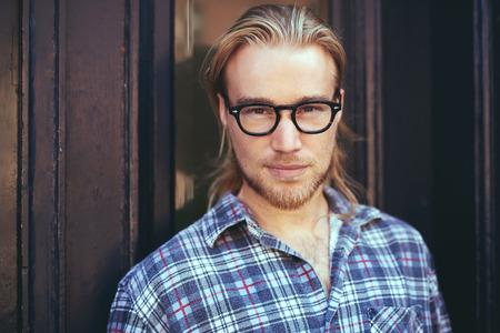 capelli lunghi: primo piano ritratto di uomo biondo con i capelli lunghi e gli occhiali. uomo riflessivo Archivio Fotografico