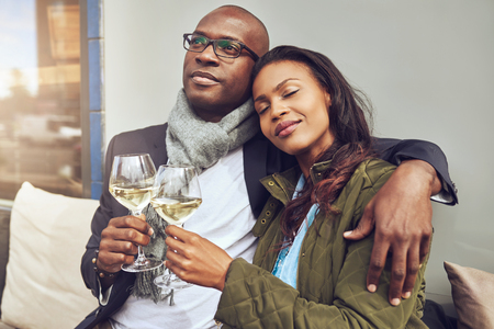 african american woman smiling: Blissful romantic young African couple relaxing in each others arms while enjoying a drink of white wine at a restaurant table Stock Photo