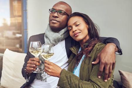 relajado: Dichoso rom�ntica pareja africana joven que se relaja en los brazos mientras se disfruta de una copa de vino blanco en una mesa de restaurante