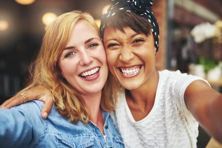 그들은 웃음과 농담 팔에 팔을 서로 카메라를 행복하게 웃어 해피 발랄한 매력적인 젊은 multiracial 여자