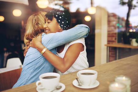 amistad: Dos multi étnico cariñosa amigas abrazar ya que sentarse en un café disfrutando de una taza de café juntos Foto de archivo