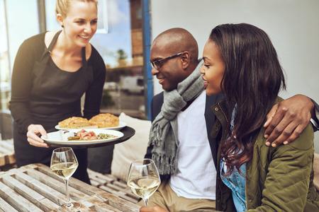 gente feliz: Camarera que sirve comida a un par brazo afroamericano cari�osa sentados en el brazo en una mesa de restaurante