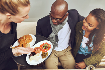 couple dining: Waitress serving plated food to young African American customers in a restaurant, high angle view showing the food on the plates