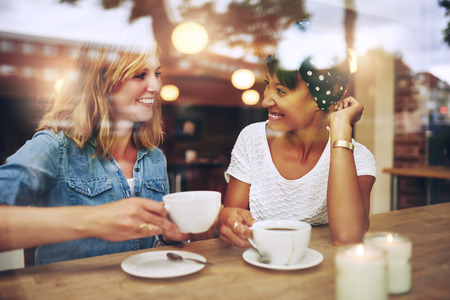dialogo: Dos de varios amigos �tnicos disfrutan de caf� juntos en una cafeter�a vistos a trav�s del cristal con reflejos mientras se sientan en una mesa charlando y riendo Foto de archivo