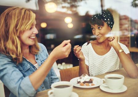 Twee charismatische multi-etnische jonge meisje vrienden zitten op een teller in een café genieten van een kopje koffie tijdens het lachen en kletsen Stockfoto