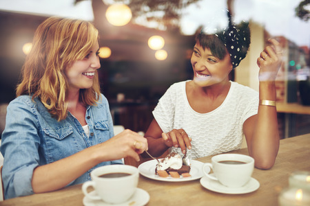 drinking glasses: Two pretty young woman enjoying coffee and cake together in a coffee house sitting at a table laughing and gossiping with happy smiles Stock Photo