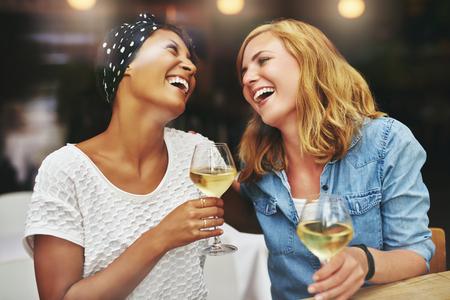 Zwei junge attraktive lebhafte multiethnischen weiblichen Freunden feiern und zusammen über einem Glas Weißwein zu lachen