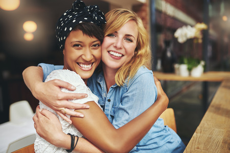 friend hug: Two happy affectionate young woman hugging each other in a close embrace while laughing and smiling, young multiracial female friends Stock Photo