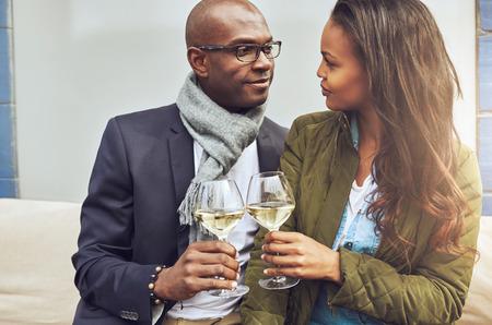 mujeres sentadas: Amorosa pareja afroamericana en un estrecho abrazo brindando con vino blanco como se ven profundamente a los ojos