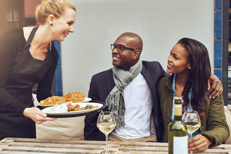 servings: Smiling happy young Caucasian waitress serving a loving African American couple dinner as they sit arm in arm at a table in a restaurant Stock Photo