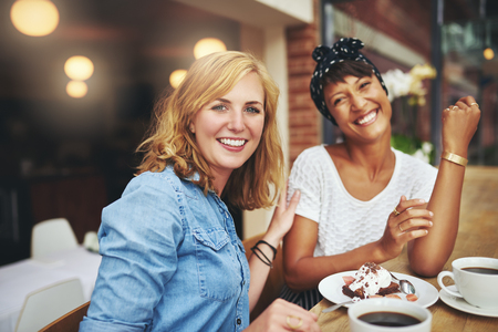 people laughing: Two attractive young multiethnic female friends enjoying coffee and cake together in a cafeteria smiling happily at the camera as they sit together at a table