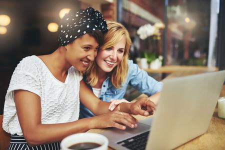 mecanografía: Dos jóvenes amigas multirraciales navega por la internet en un ordenador portátil, ya que sentarse en una cafetería disfrutando de una taza de café