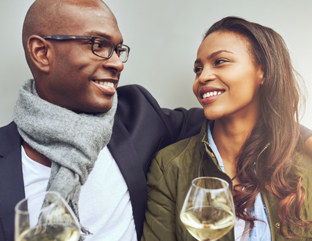 parejas de amor: Brazo rom�ntica joven afroamericano pareja sentada en el brazo disfrutando de vasos de vino blanco y sonriendo amorosamente a los ojos, vista de cerca Foto de archivo