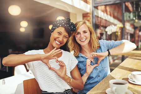 Young romantic female friends sitting in a restaurant together enjoying coffee making heart shaoed signs with their hands as they laugh at the camera, multiethnic couple Stock Photo