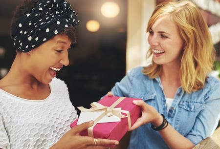Jolie jeune femme blonde donnant un jeune ami, séduisant, africaine américaine un cadeau surprise-cadeau enveloppé avec du papier rouge, un arc et carte