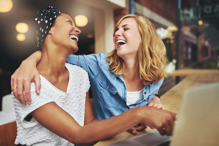 Two affectionate multiracial women friends hugging and laughing as they point at a laptop computer screen that they are sharing Stockfoto
