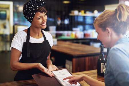 in order: Customer checking a wine menu in a pub being presented to her by an attractive friendly young African American small business owner Stock Photo