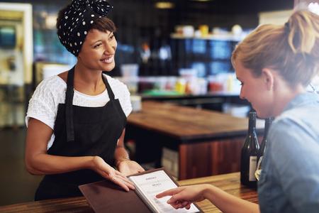 Klant controleren van een wijnkaart in een pub aan haar wordt gepresenteerd door een mooie vriendelijke jonge Afro-Amerikaanse kleine ondernemer