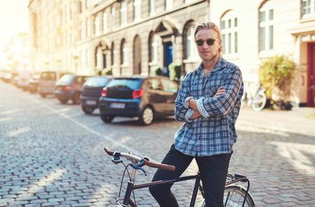 Portrait des Mannes auf seinem Fahrrad mit gekreuzten Armen stylish suchen. Stadt Lebensstil