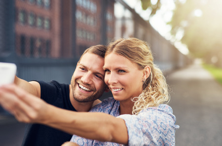 street people: Beautiful Couple Taking a Selfie While Sitting in a Park