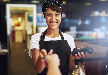 Lächelnde Kellnerin oder Inhaber eines kleinen Unternehmens, die ein Kreditkarte von einem Kunden, um durch die Banken Maschine in Zahlung für einen Auftrag zu verarbeiten