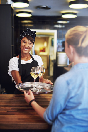 waitress: Smiling bartender, waitress or female business owner serving glasses of white wine on a tray to a customer with a lovely friendly smile as she stand behind the wooden counter in a bar Stock Photo