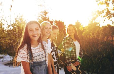 juventud: Adolescente que mira la cámara con amigos en el fondo