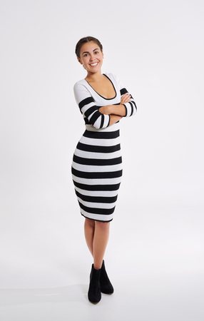 legs folded: Confident young woman with a lovely smile standing with folded arms and crossed legs in a stylish striped dress, full length over grey Stock Photo