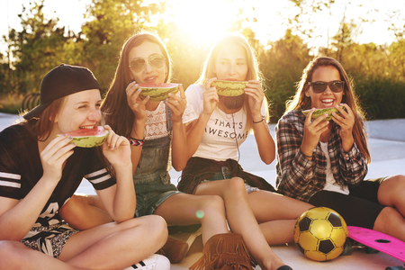 devouring: Teenage girls hanging out in a park on a summer evening Stock Photo