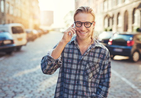 self assured: Blondie young man with mobile phone in the street