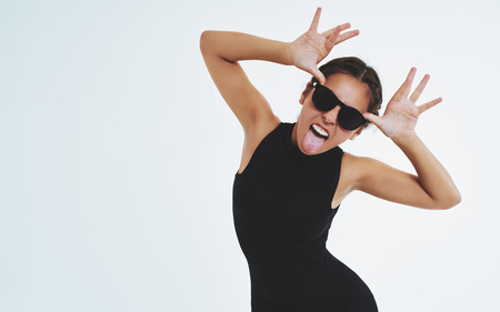 Impudent cheeky young woman in trendy clothing and sunglasses sticking out her tongue at the camera and fluttering her hands on either side of her forehead, over white with copyspace