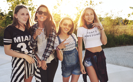 slim girl: Group of girls posing and fooling around outside, summer evening