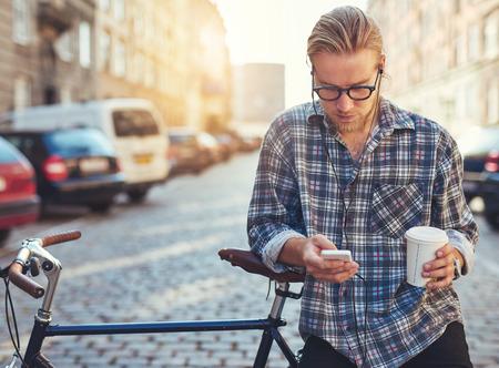 escucha activa: Retrato al aire libre del hombre joven moderna con el teléfono móvil en la calle, sentado en la bicicleta