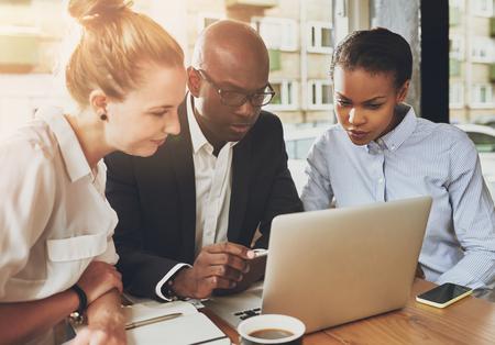 Zwarte en witte mensen uit het bedrijfsleven samen te werken op een klein kantoor