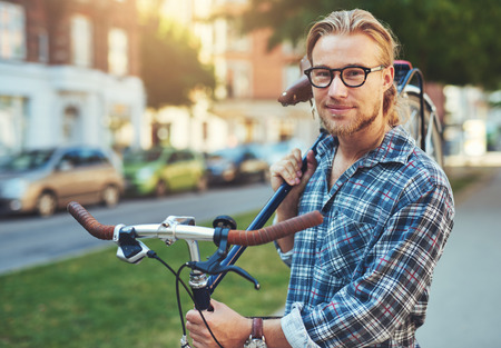 upper: Portrait of blonde white man in the city with a bike