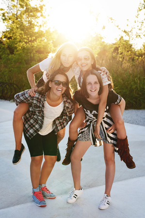 piggy back: Friends piggyback each other in a park on a summer day Stock Photo