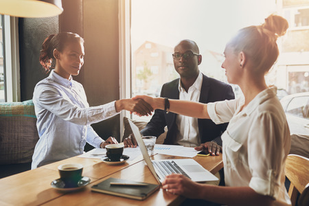 men shaking hands: Black business woman and white business woman shaking hands closing a deal Stock Photo