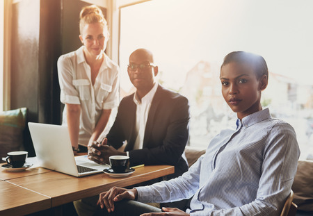ethnic woman: Portrait of serious business people, multi ethnic, sitting at a coffee shop working Stock Photo