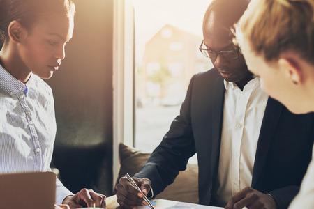 ?  ?       ?  ?      ?  ?     ?  ?    ?  ? �female: Negro ejecutivo explicar plan de negocios en frente de dos inversores femeninos Foto de archivo
