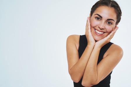Mooie vrouw met een mooie huid, glimlachend in de camera met haar wangen. Ruimte kopiëren. Geïsoleerde portret Stockfoto