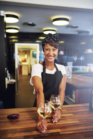 Pretty successful African American businesswoman standing behind the wooden counter in her pub serving glasses of white wine to a customer with a warm friendly smile, small business owner