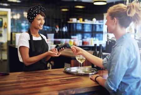 Cliente en un bar de pagar el dueño del negocio o camarera con una tarjeta de crédito para ser procesada en una máquina de la banca de mano, se centran en el atractivo de África propietario americano
