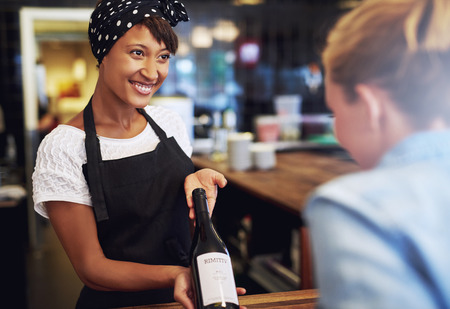 Smiling attractive young African American waitress or bartender showing a bottle of red wine to a customer in a bar before opening it, conceptual of employment or a small business owner photo