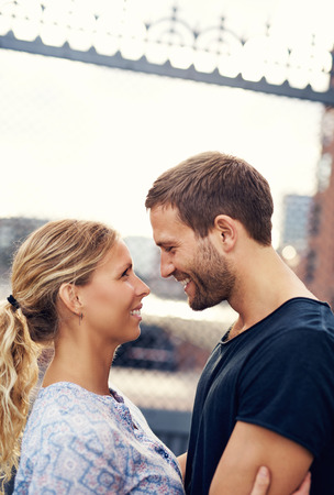 gazing: White Loving Couple In The City, Looking In Each Others Eyes Stock Photo