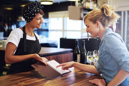 Cliente femenino elegir el vino de una carta de vinos que se presenta a ella por una encantadora joven camarero afroamericano en un bar conceptual de empleo, la propiedad de la pequeña empresa o un empresario