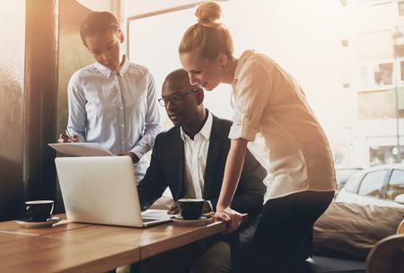 Gruppe von Unternehmern arbeiten mit einem Laptop und hält ein Dokument