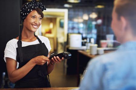 pagando: Sonriente atractiva afroamericana pequeño empresario tomar pago de un cliente procesar una tarjeta de crédito a través de la máquina bancaria de mano Foto de archivo