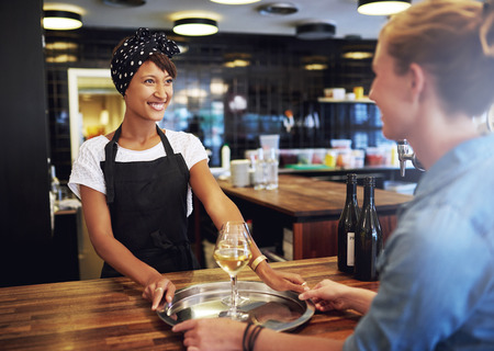 Cheerful Waitress Serving Glasses of Wine on a Silver Tray to a Female Customer inside the Pub. photo